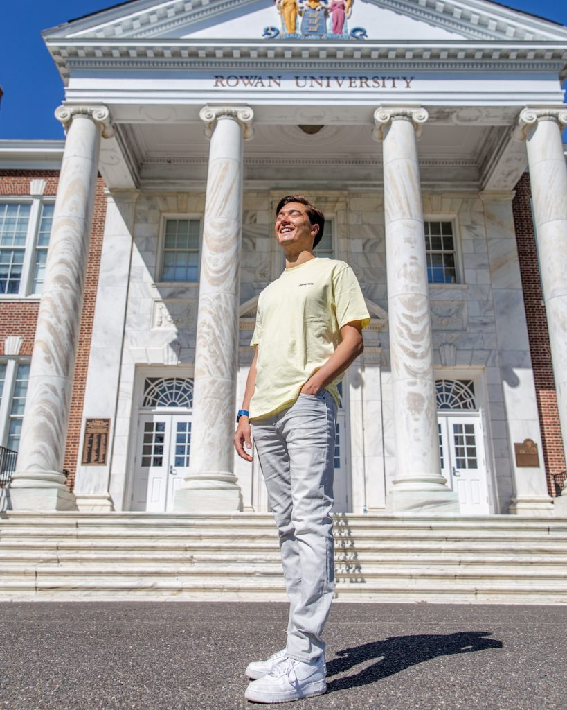 Anthony gazes into the sun in front of Bunce Hall wearing all light colors.
