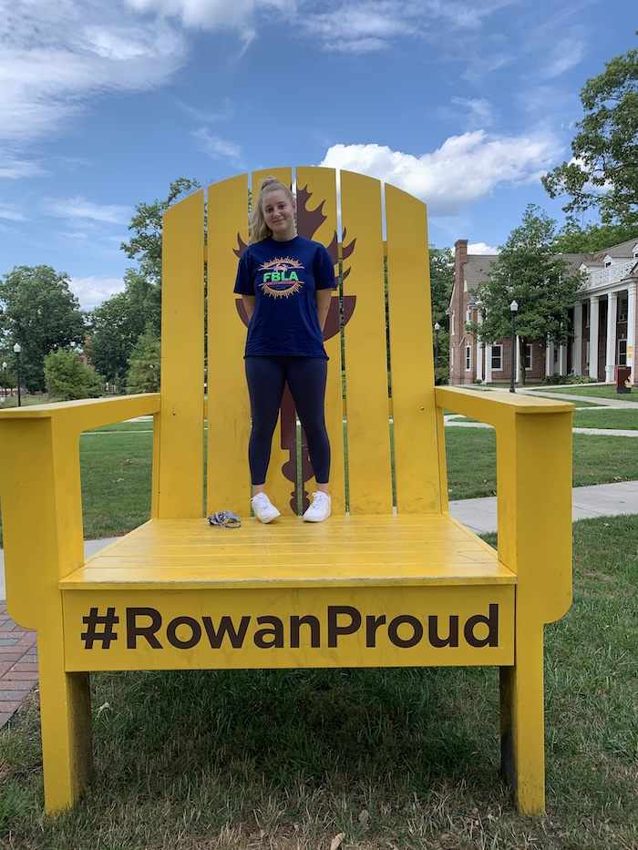 Emily stands on the #RowanProud chair on campus.