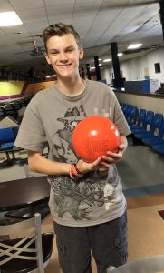 A picture of Joseph holding a bowling ball.