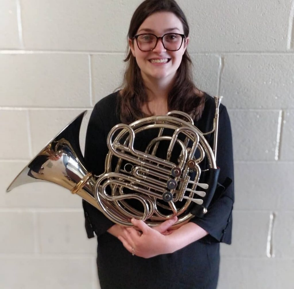 Abby standing with French horn in hands.