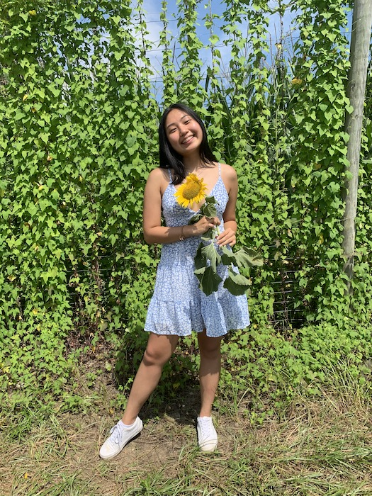 Lucinda smiles wearing a blue dress and holding a sunflower.