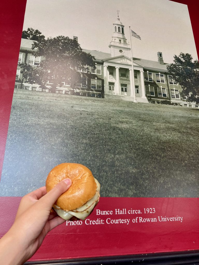 Holding a burger up to the photo of Bunce Green inside Alumni Grill.