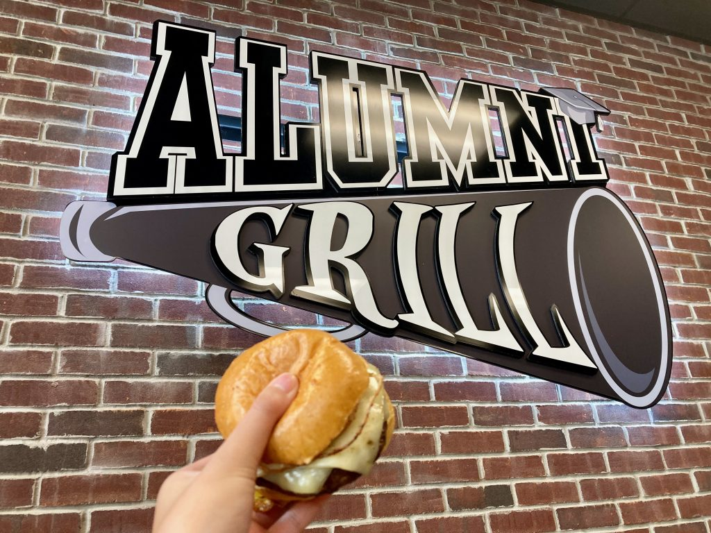 Holding up a burger to the Alumni Grill sign.
