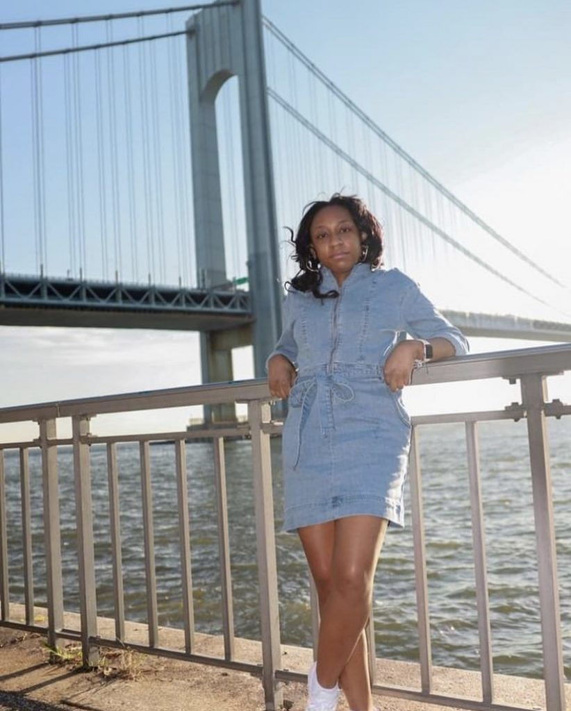 Vaniece stands and leans against a railing in front of a riverfront.