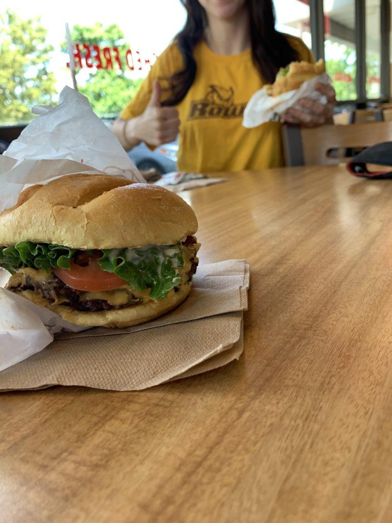 Jen enjoying her burger from Smashburger while wearing a yellow Rowan shirt.