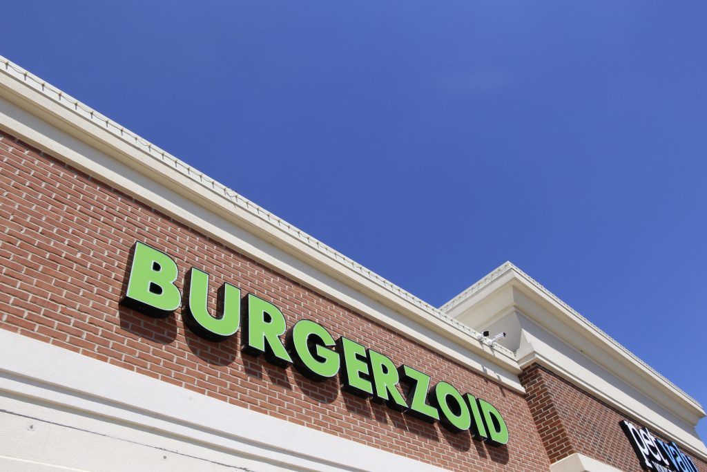 Bright green Burgerzoid sign over the store.