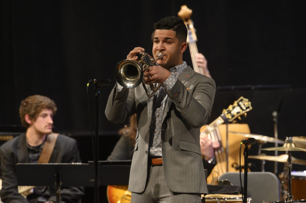Luis playing his trumpet in a performance.