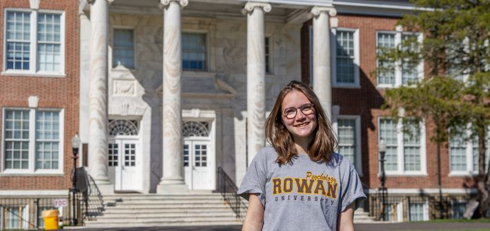 Leah smiles in front of Bunce Hall while wearing a gray Rowan shirt and glasses.