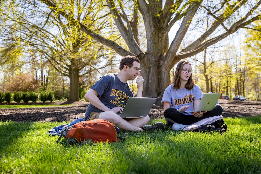 Kevin and Leah study on their laptops sitting on Bunce Green.