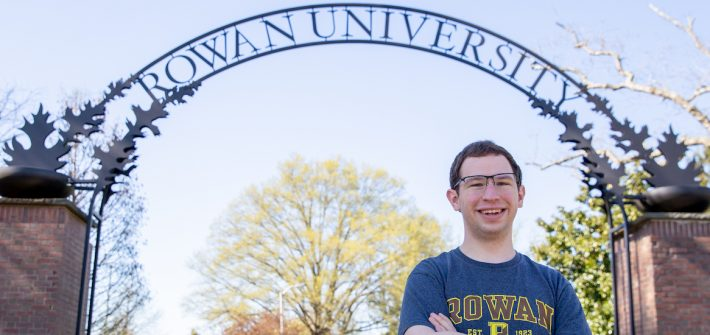 Kevin stands in front of the Rowan arch in a Rowan t-shirt.