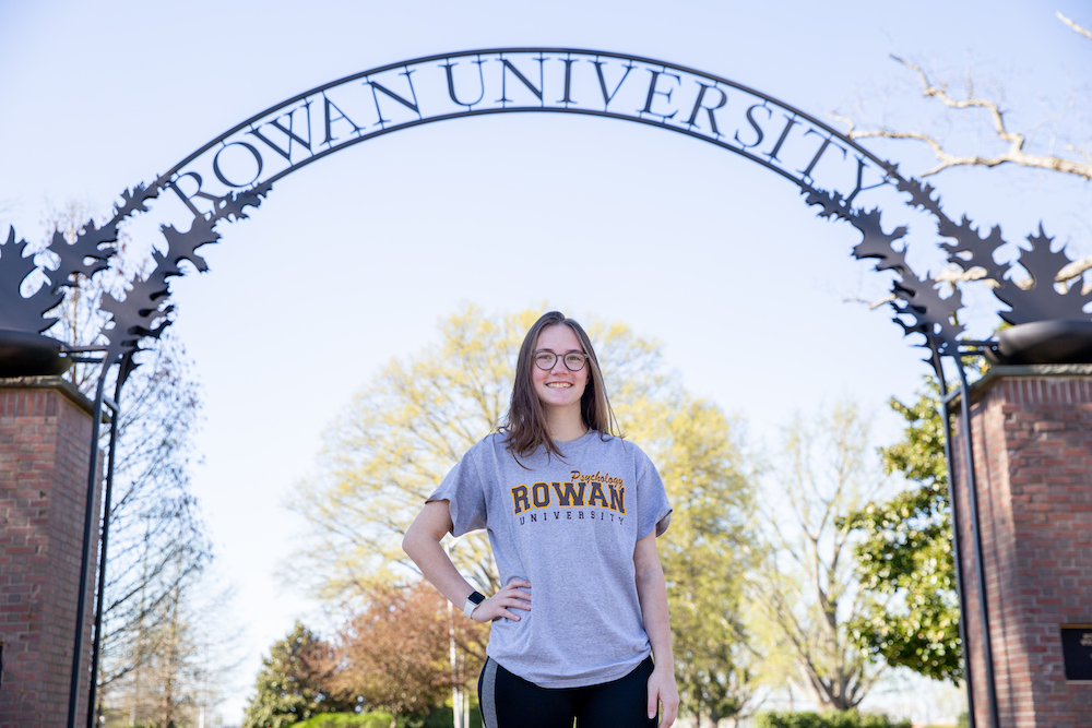 Leah puts a hand on her hip while standing under the Rowan arch.