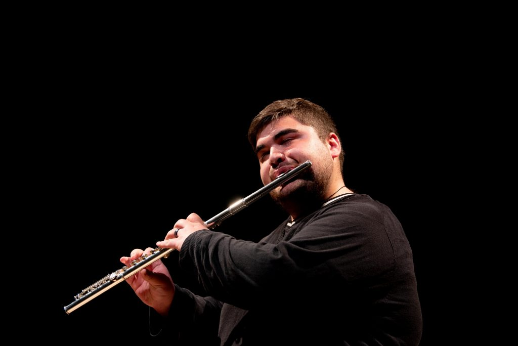 Liva playing their flute on stage.