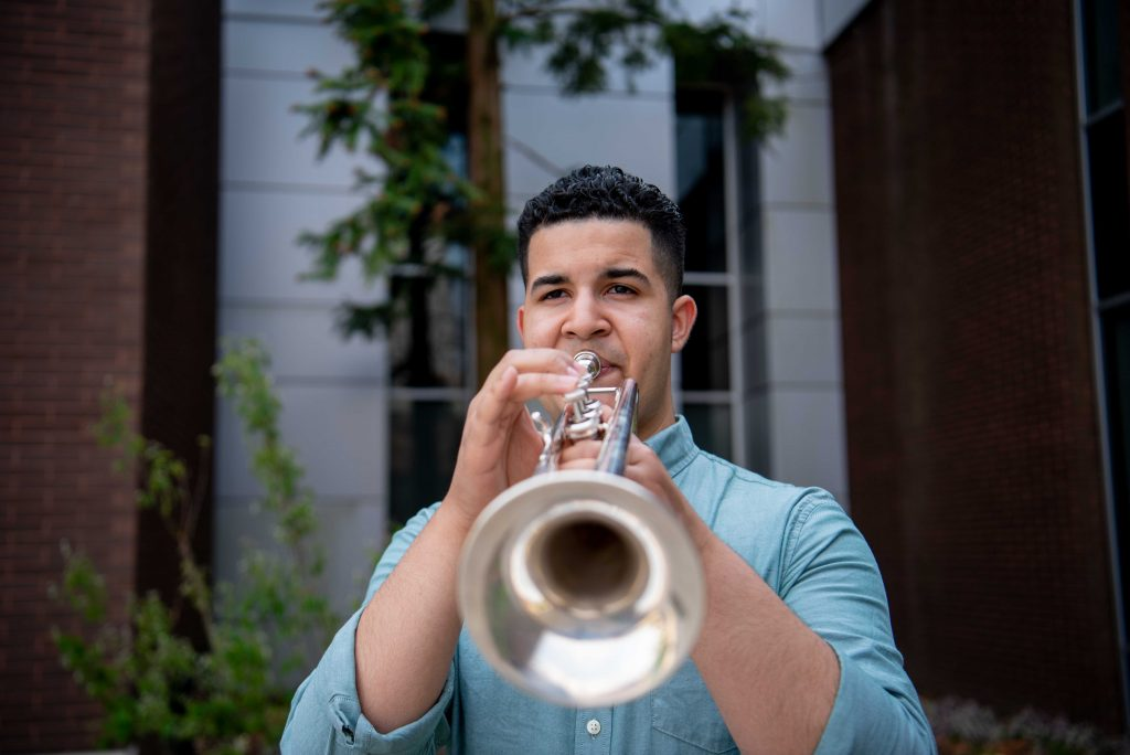 Luis playing his trumpet outside of Wilson Hall.