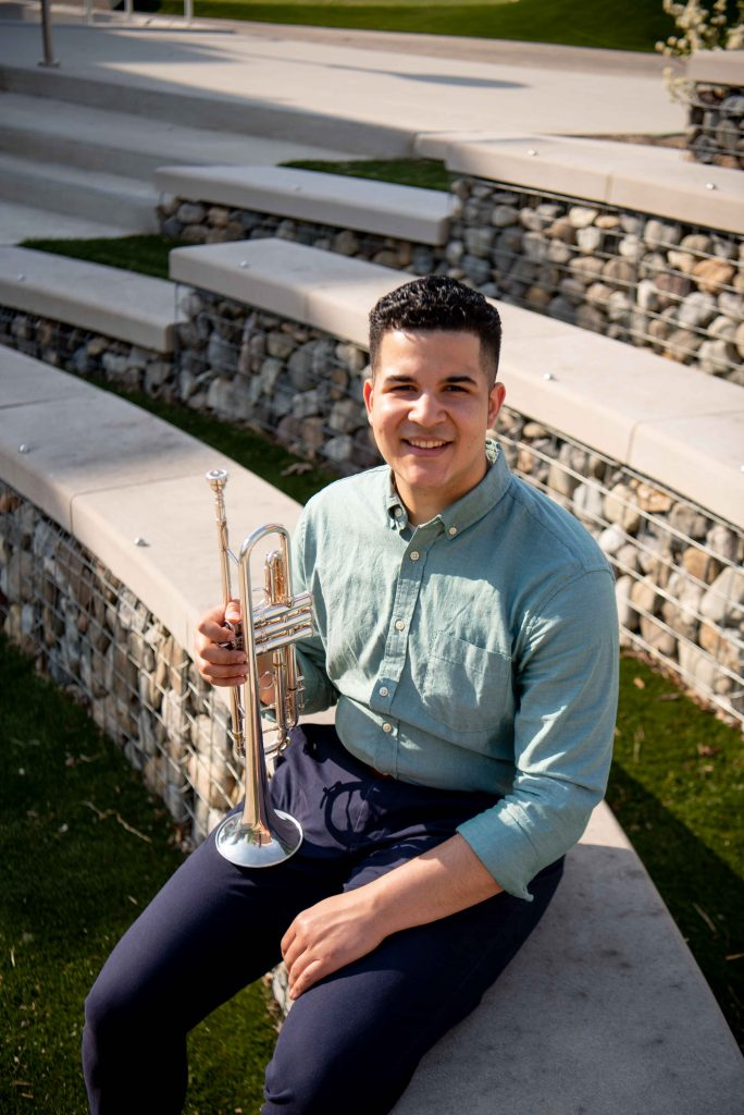 Luis posing with his trumpet outside.