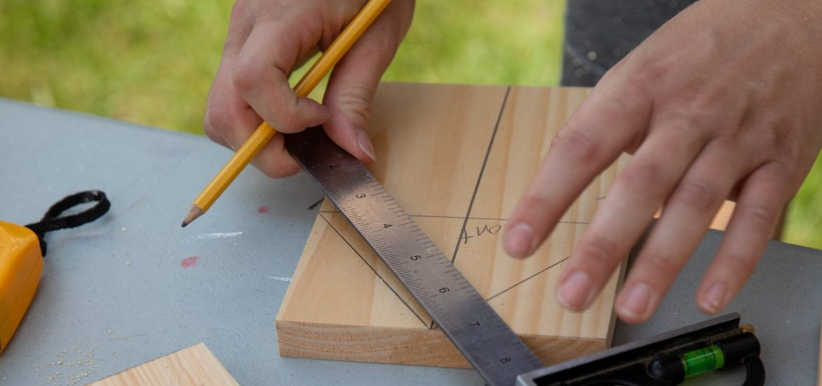 Someone measures a line on a piece of wood.