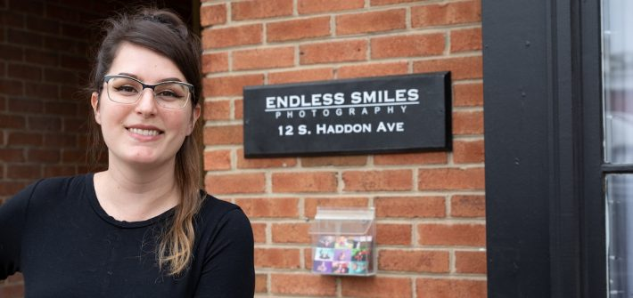 Gabi stands in front of the Endless Smiles Photography Sign