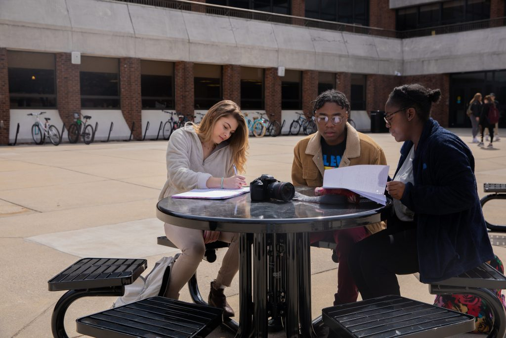 Students study at one of the tables behind the Student Center.