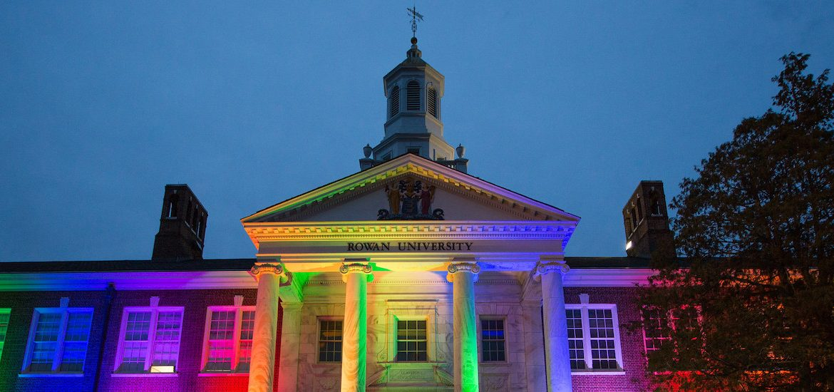 An exterior shot of Bunce Hall is illuminated in rainbow colors for Pride Month.