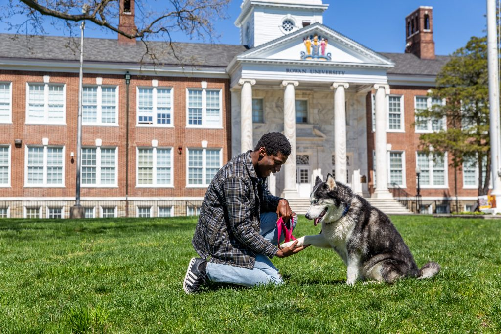 A student plays with his dog on Bunce Green.