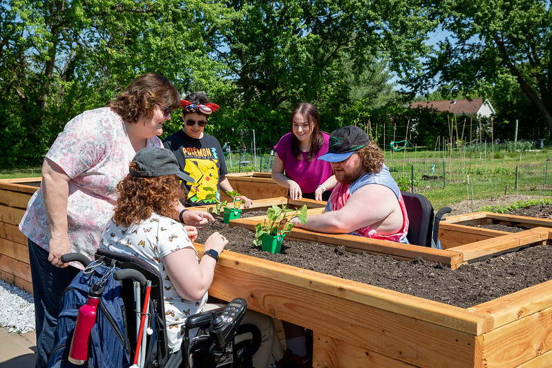 Jenna talks with the Borgersen family by the raised garden beds.