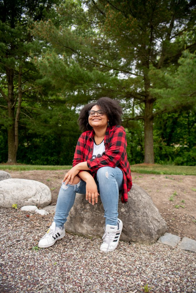 Girl in flannel shirt sitting on a rock and smiling.