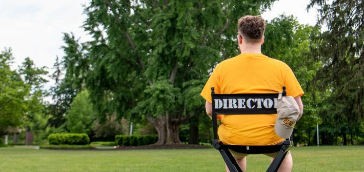 Nick sits in a director's chair on Bunce Green.