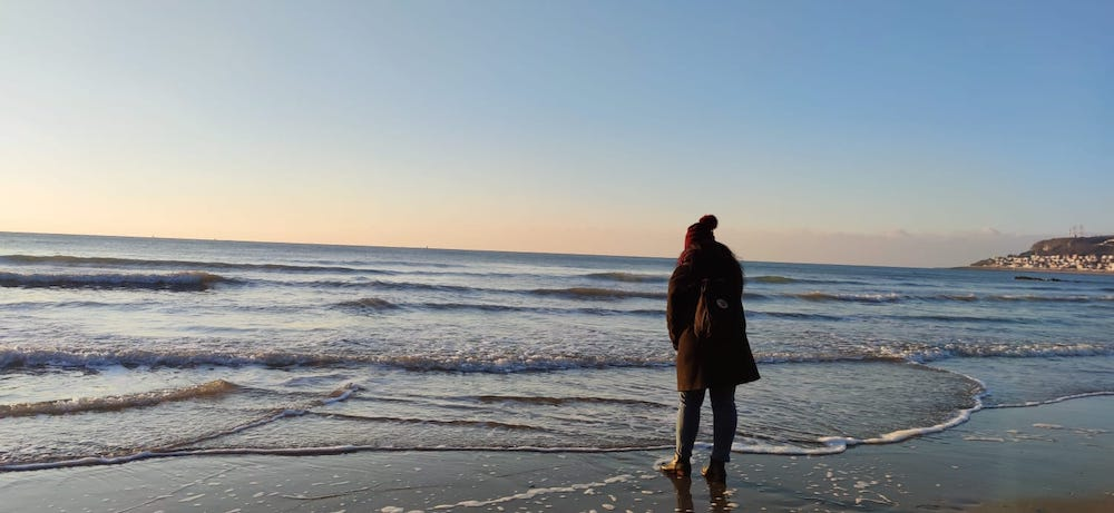 Stephanie wears a dark red winter hat to the cold beach in Le Havre, France.