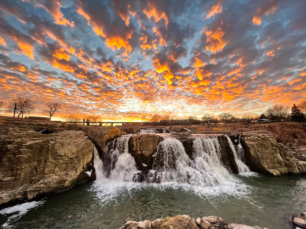 A gorgeous blue and orange sunset shines above a majestic waterfall in Minnesota.