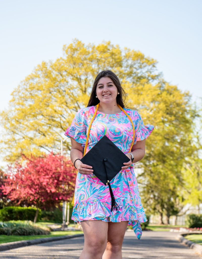 Kassidy poses with her graduation cap in front of some trees.