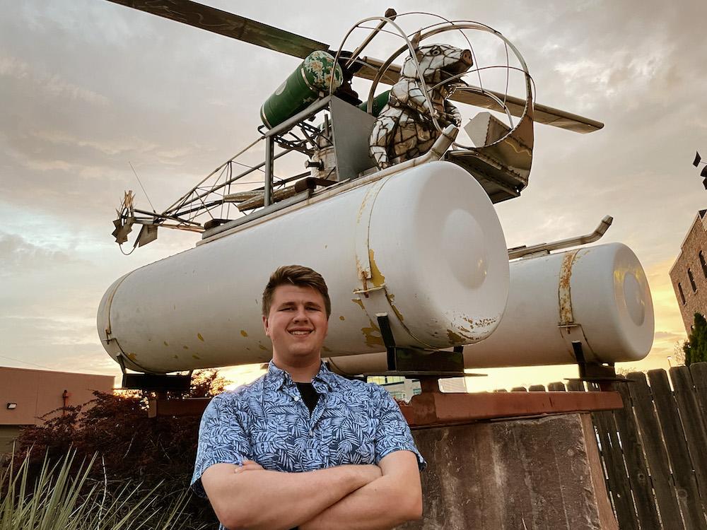 """Mitch poses under the """"Pork Chopper"""" statue in Sioux Falls, South Dakota."""