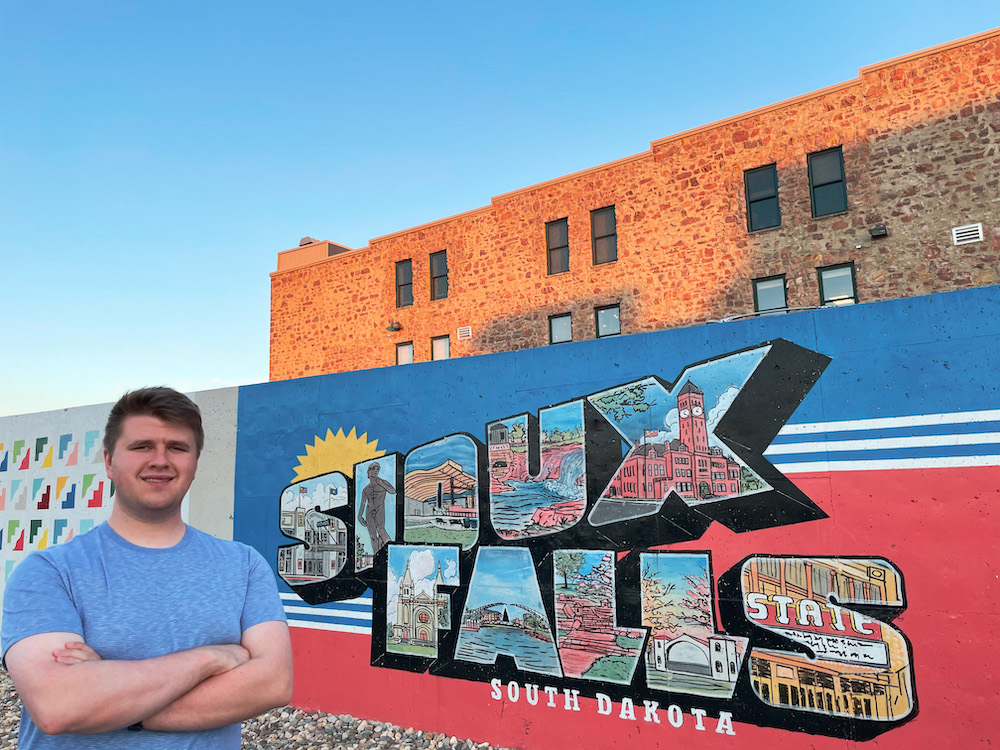 Mitch poses confidently in front of a Sioux Falls sign.