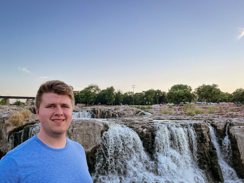 Mitch wears a light blue shirt and stands in front of a waterfall.