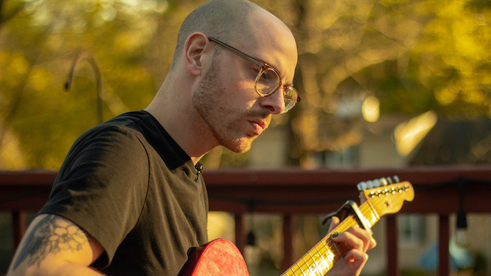 Adam, wearing glasses and a black t-shirt, plays the guitar on his porch.