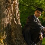 Riel wears his graduation regalia and squats by a tree.