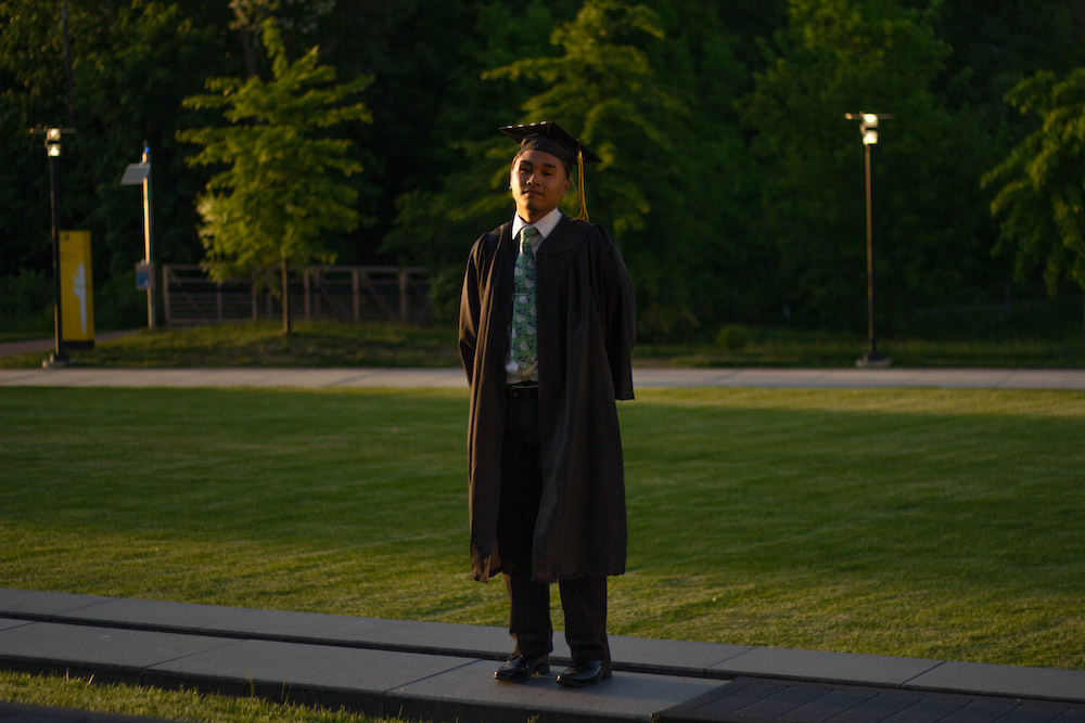 Riel stands on the lawn of Business Hall while wearing graduation regalia.