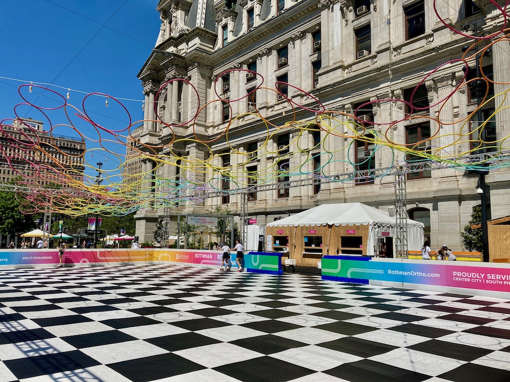Rothman Roller Skating Rink in Dilworth Park with a checkerboard floor and neon rainbow decor.