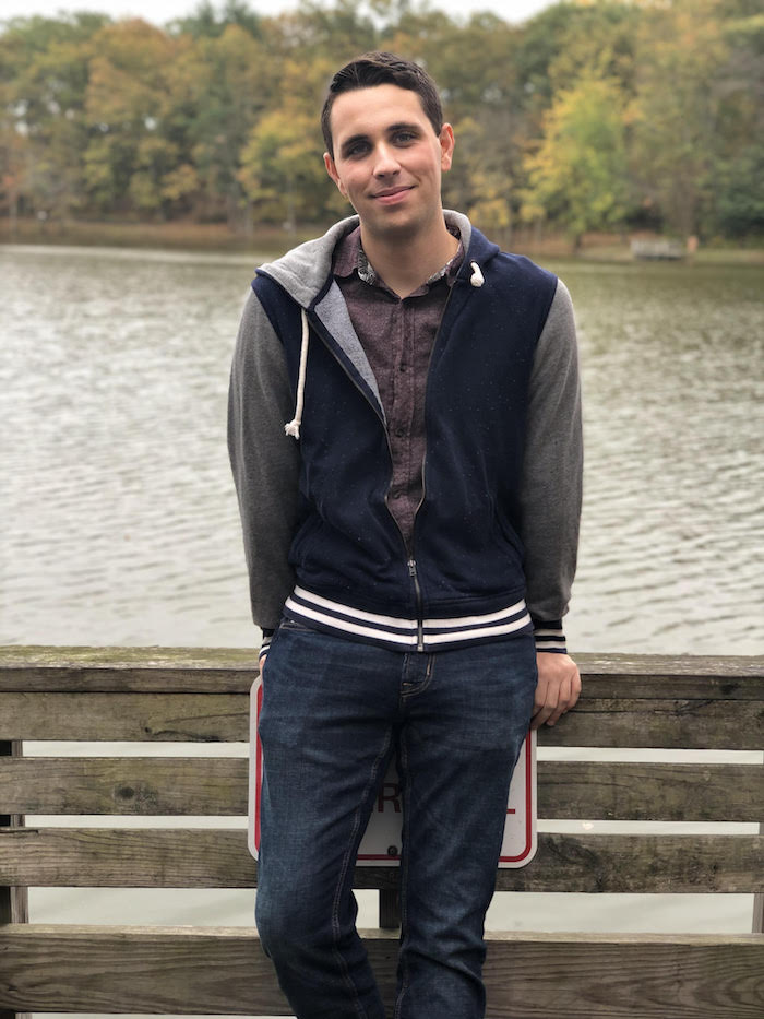 Ian leaning against a bridge overlooking a lake.
