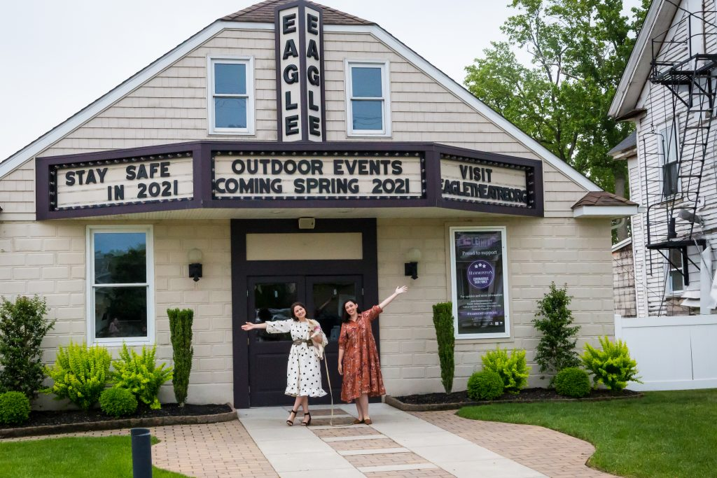 From left to right stands Angela and Molly Jo. They stand out front of the Eagle Theatre under the marquee with the theater's name, next to green grass and bushes, and having their outside arm raised in a welcoming manner.
