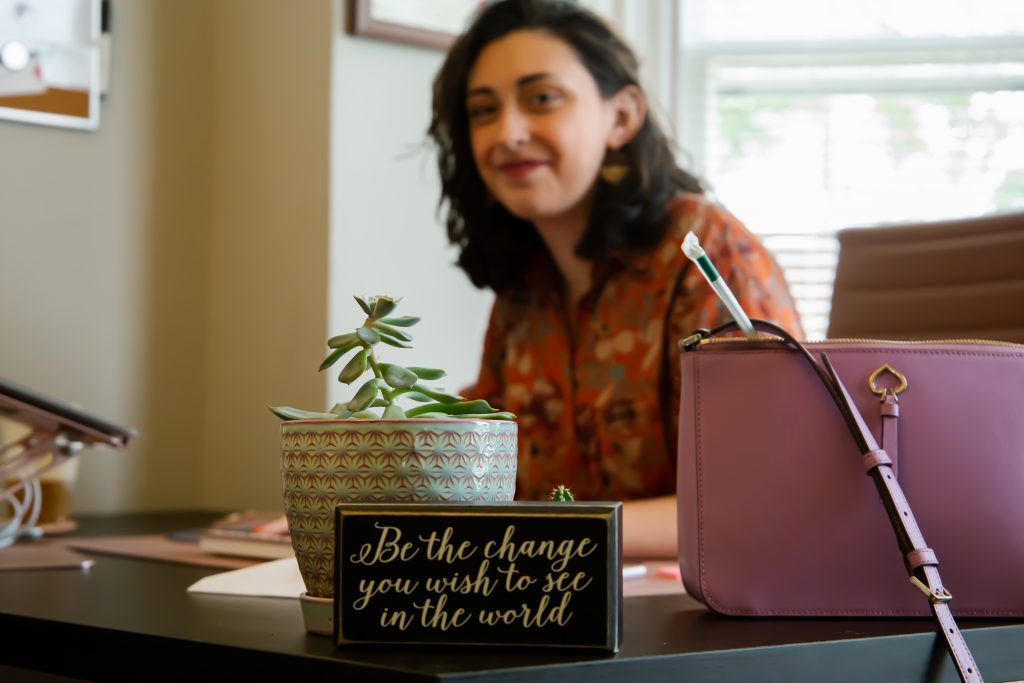 """In the front is a focus on a sign on Molly Jo's desk that says """"Be the change you wish to see in the world."""" She sits behind it out of focus with a smile on her face."""