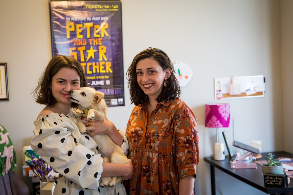 From left to right stands Angela and Molly Jo smiling in their office at the Eagle Theatre. Angela is holding her white puppy who is licking her face.