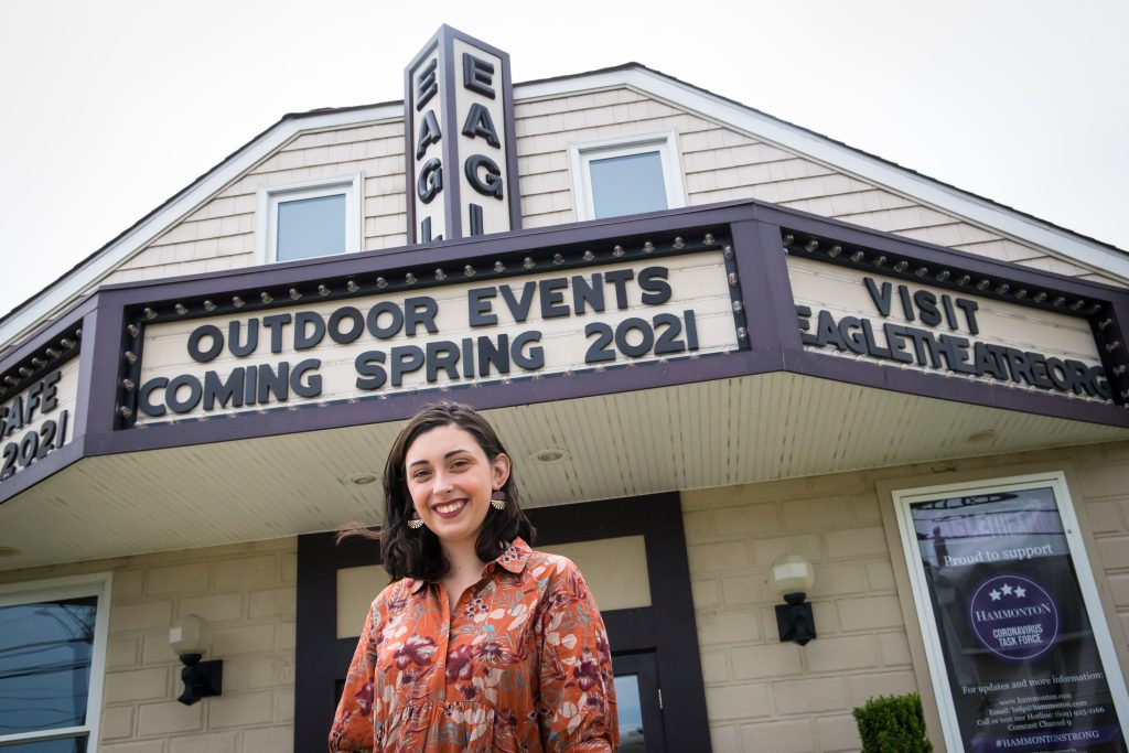 Molly Jo is standing out front of the Eagle Theatre smiling while under the marquee featuring the coming outdoor events.