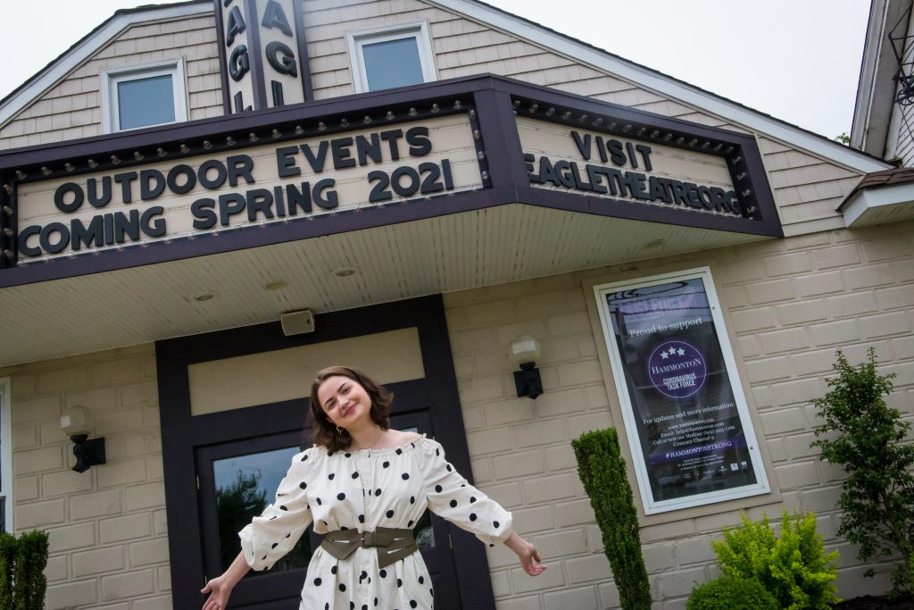 Angela stands smiling with open arms out front of the Eagle Theatre under the marquee.