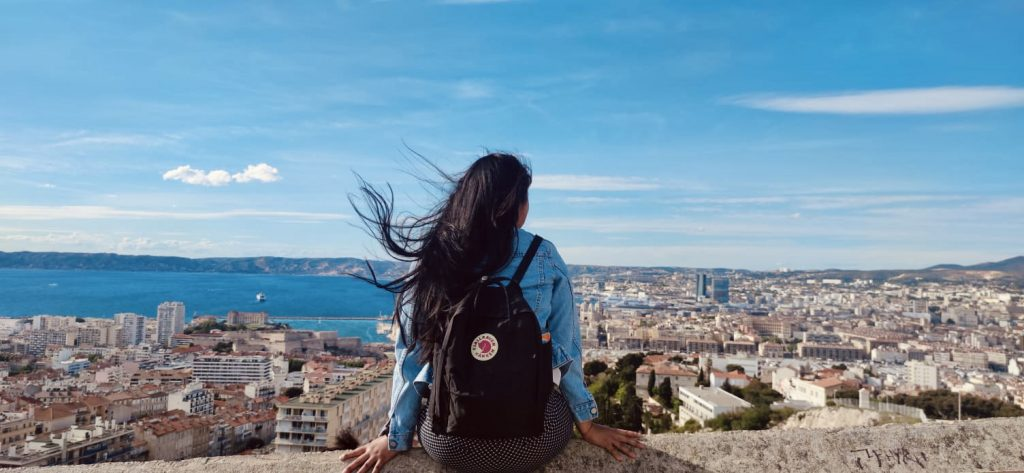 Stephanie sits on a wall overlooking the whole city of Marseilles, France.