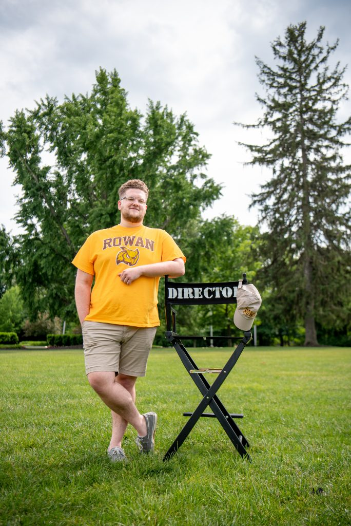 Nick Flagg standing with a directors chair.