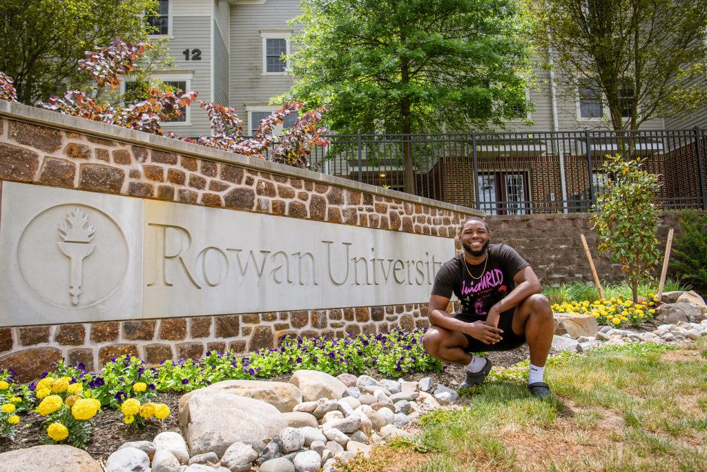 Reshaun crouches for a photo in front of the Rowan University sign near the Townhomes.