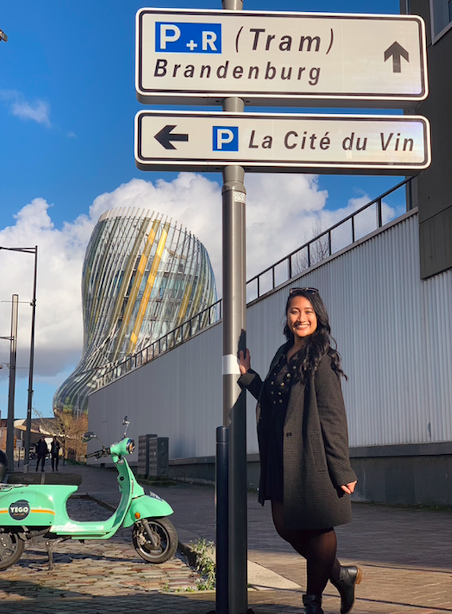 Stephanie poses under a transportation sign in Bordeux, France with a reflective structure in the background.