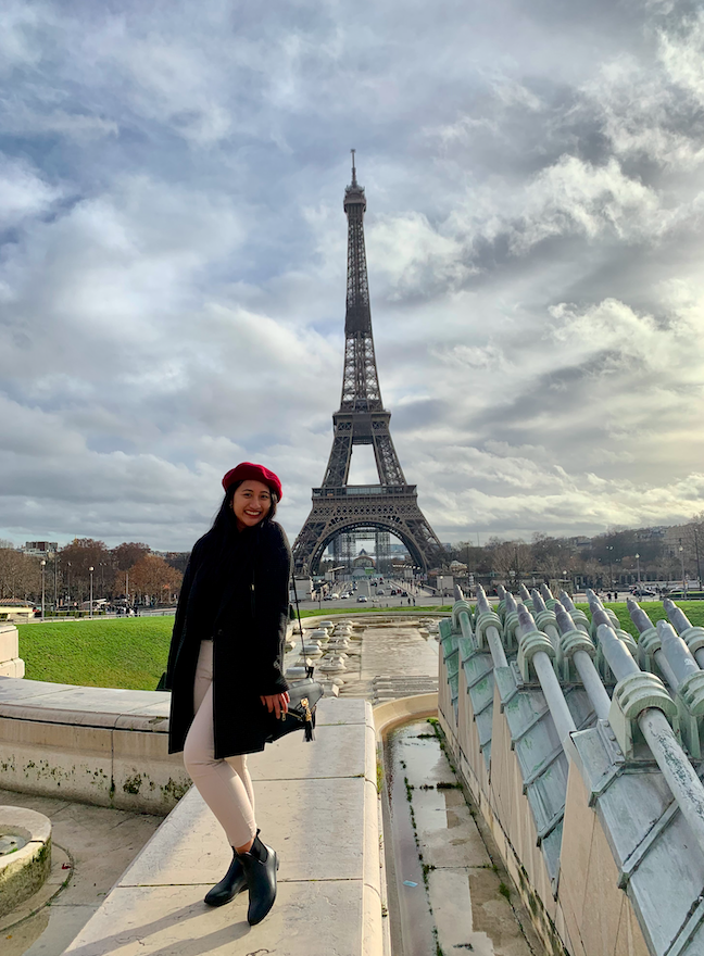 Stephanie wears a red beret in front of the Eiffel Tower in Paris, France.