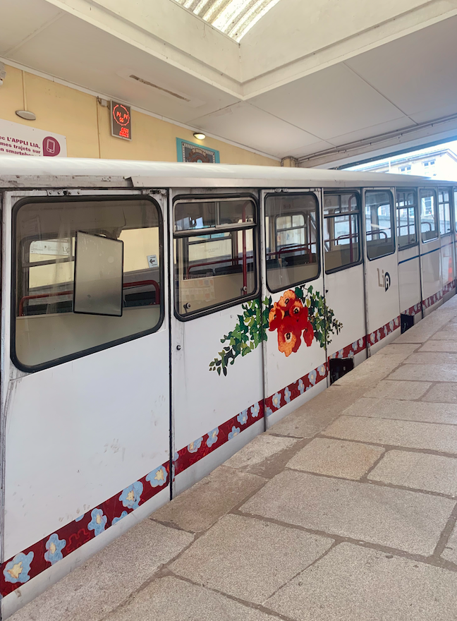 """Picture of """"La Funiculaire"""" (little train Stephanie had to take to get up to her apartment). It is about 5 feet wide and maybe 6 feet tall with paintings of flowers on the side."""
