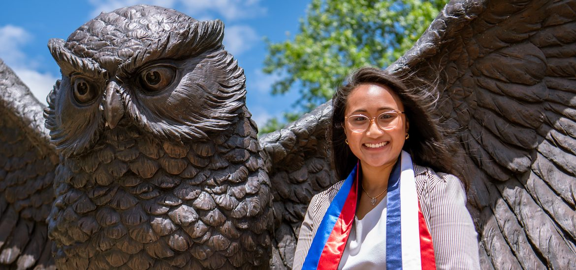 Stephanie sits at the Giant Prof statue on campus while wearing a custom stole showing the Filipino and French flags.