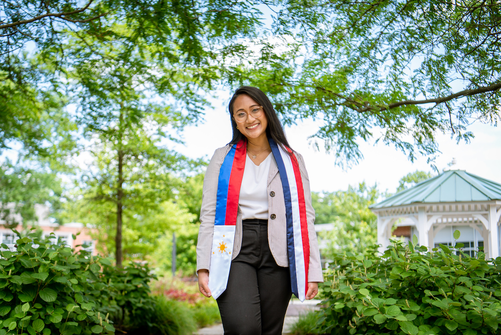 Stephanie wears a custom stole with the Filipino and French flags on the sunny and green Rowan campus near Bunce Hall.